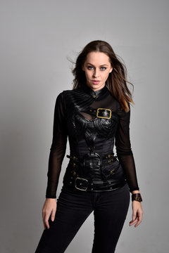 portrait of a pretty brunette woman wearing black leather fantasy costume  on a studio background.