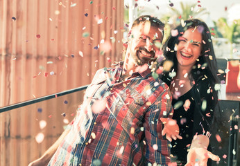 Millennials young people having fun celebrating in the discoteque. Happy couple doing party throwing confetti in the outdoor. Entertainment and festive holidays concept - Image