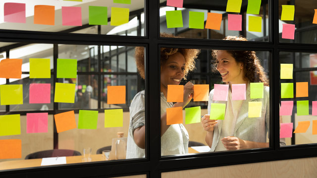 Friendly mates discuss business ideas writing its on sticky notes