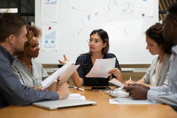 Fototapeta Multiethnic team led by asian ceo discussing financial statistics obraz