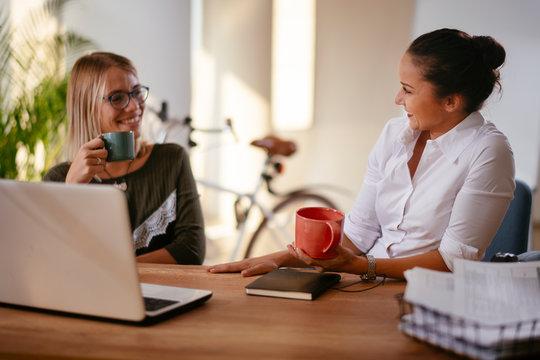 Two young women having coffee break in office