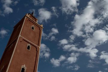 Moroccan square minaret taken from below with beautiful blue sky and clouds