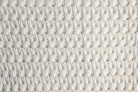 Cropped close up shot of seamless woolen knitting pattern of fall / winter season warm sweater, clearly visible fiber texture of stylish hipster knitwear clothing. Background, copy space, top view.