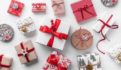 Fototapete - Christmas gift boxes with red ribbon and decoration on white background. Xmas and Happy New Year holiday. Flat lay, top view