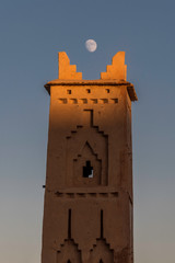 Moroccan village tower with moon framing the top spires