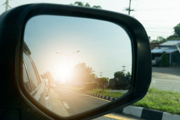 Close beside car form mirror view with other cars and sun light on the road. Wall mural