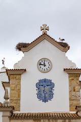 Nest of a White Stork (Ciconia ciconia) on a church roof in the old town in Olhao, Algarve, Portugal.