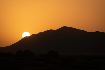 Silhouetted sunrise emerging behind the Atlas Mountains