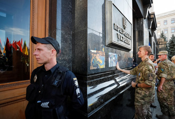 An activist sticks a picture of serviceman killed in conflict in eastern Ukraine on the building of presidential administration during a rally against the approval of the so-called Steinmeier Formula, in Kiev