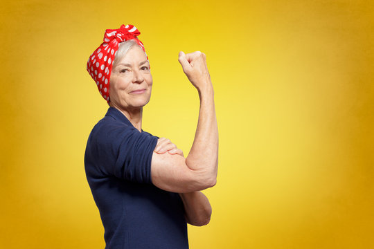 Senior rosie riveter concept: self-confident elderly woman with clenched fist rolling up her sleeve, copy space