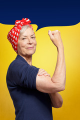 Senior rosie riveter concept: mature woman with clenched fist rolling up her sleeve, background template, copy space