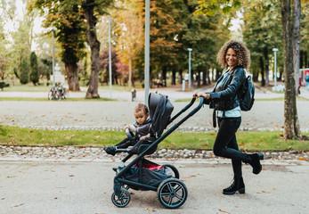 Portrait of beautiful mother walking stroller in park, smiling and walking pram
