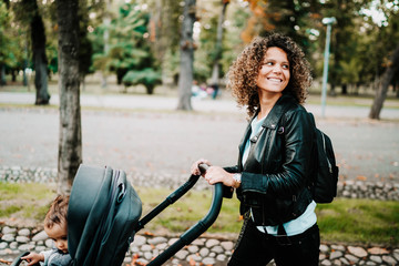 Portrait of beautiful smiling mother pushing stroller in city park