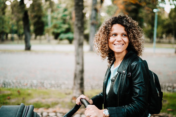 Portrait of young curly haired mother smiling and walking in park with baby in stroller