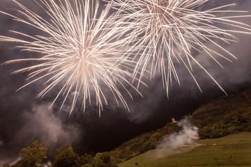 Awesome brilliant white fireworks above trees and a illuminated church, Vittorio Veneto, Italy