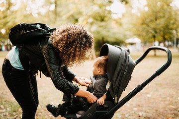 Portrait of young curly haired mother talking with baby in stroller