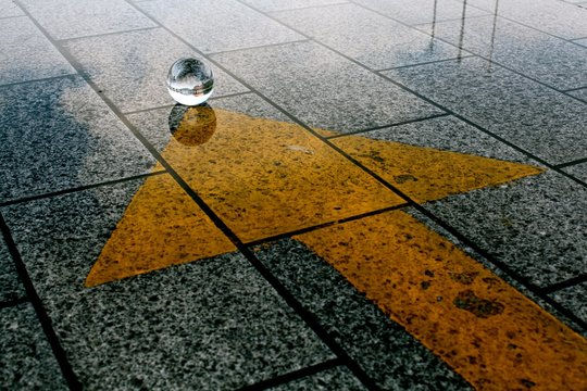 High angle shot of the stone ground with a yellow arrow pointing towards a mysterious crystal ball