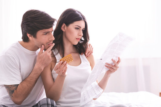 Focused millennial couple reading leaflet before taking contraceptive pills