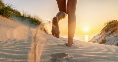 Woman runs towards to the Baltic Sea Beach at Sunset