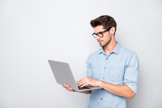 Photo of thoughtful focused clever interested freelancer holding laptop with hands wearing eyeglasses working on deadline project isolated grey color background