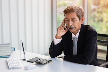 business man concept.old asia businessmen wareing black suit sitting in offic and touch their heads, serious, headache working hard unhappy. copyspace