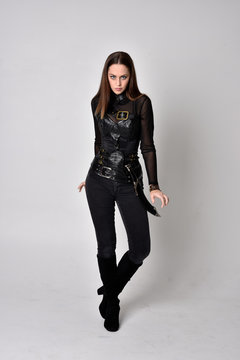 full length portrait of a pretty brunette woman wearing black leather fantasy costume with a dagger. standing pose on a studio background.