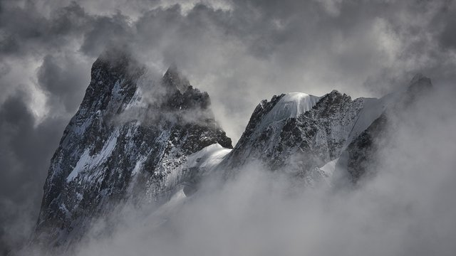 Magical shot of a beautiful snowy mountain peak covered with clouds.