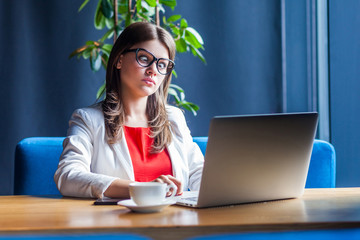 Portrait of crazy beautiful stylish brunette young woman in glasses sitting and looking at laptop display with crossed eyes funny face. indoor studio shot, cafe, office background.