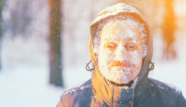 Fun portrait of an young frozen man. Jogging in a blizzard in the woods. Face covered with snow and frost. Closeup portrait of happy young guy smiles in cold weather in the winter forest at sunset.