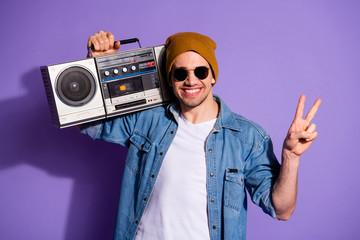 Photo of confident cheerful kind friendly man showing you v-sign smiling toothily holding retro recorder with hands wearing white t-shirt isolated over purple vibrant color background