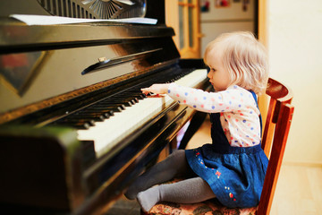 Adorable little girl playing piano
