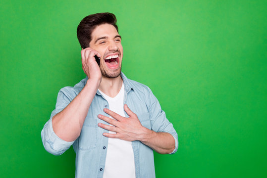 Photo of handsome guy holding telephone hand near ear listen best friend humorous story laughing out loud wear denim shirt isolated green color background