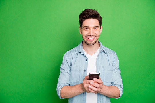 Photo of cheerful brown haired handsome blogger browsing through his telephone looking for ideas to post in his social media isolated over green vivid color background