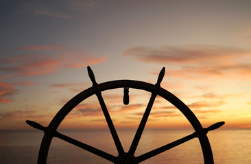 Ship rudder with sunset sea on background.