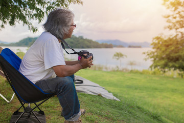 asian senior man holding digital camera, he sitting on seat on nature background, he try to take a photo in lakeside, happiness retirement activity