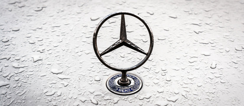 Mercedes Benz logo on the hood with raindrops