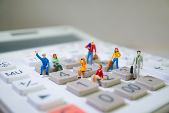 Miniature people, business team on calculator using as business concept