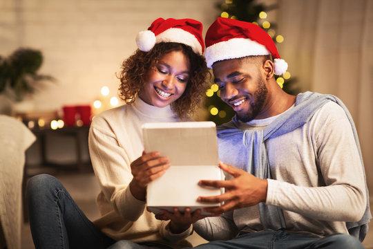 Christmas magic. Afro couple opening gift box