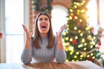 Young beautiful woman sitting at the table at home around christmas tree and decoration crazy and mad shouting and yelling with aggressive expression and arms raised. Frustration concept.