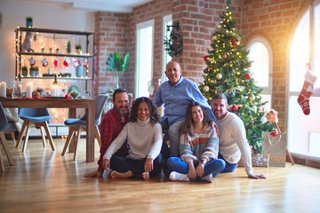 Beautiful family smiling happy and confident. Sitting on the floor and posing with tree celebrating Christmas at home