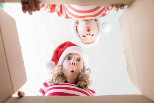 Surprised children unpack Christmas gift box