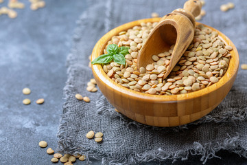 Organic brown lentils and wooden scoop in a bowl.