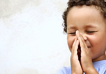 boy praying to God stock image with hands held together with closed eyes