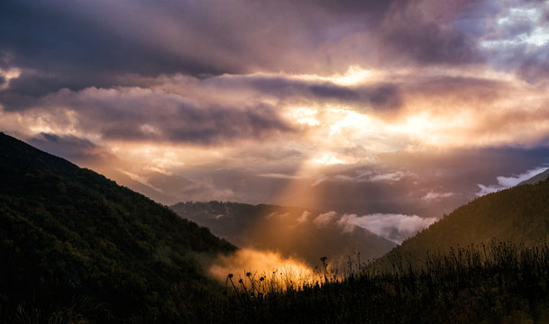 Fairy landscape with dramatic sky and sunbeam in mountains