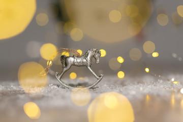 Decorative figurines of a Christmas theme. Figurine of a rocking horse. Decoration for a Christmas tree. Festive decor, warm bokeh lights.