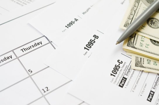 IRS Form 1095-A 1095-B and 1095-C blank lies on empty calendar page with pen and dollar bills