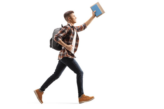 Male student running and holding a book