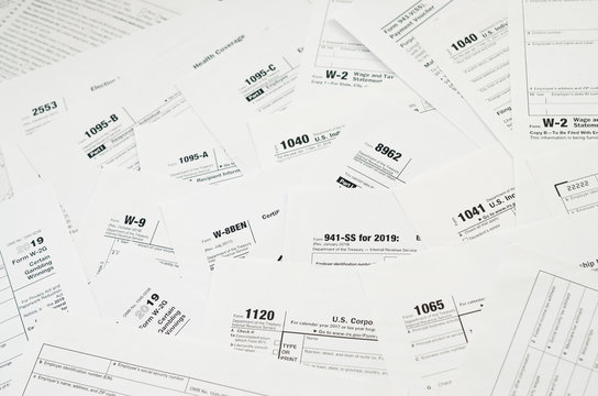 Many tax form blanks lies on table close up. Tax payers paperwork routine and bureaucracy concept