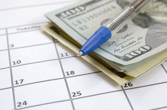 Pen and many hundred US dollar bills on calendar page close up