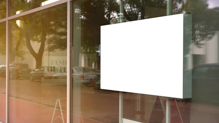 empty white poster frame on glass of showcase window of shopping mall fashion outlet centre mock-up